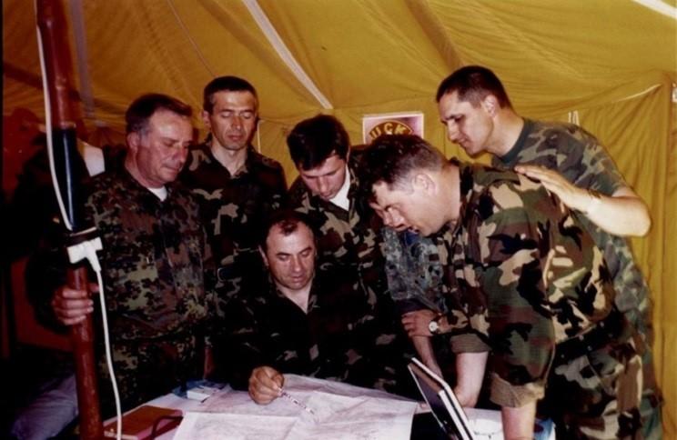 Në çadrën e Shtabit të Stërvitores së UÇK-së në Helshan. Kolonel Maliq Doçi duke elaboruar lidhur me veprimet luftarake, derisa nga e majta janë: kolonel Spiro Butka, Bilall Syla, Rifat Sylejmani, Enver Berisha, unë (Agim Sylejmani) dhe Shaban Musliu.
